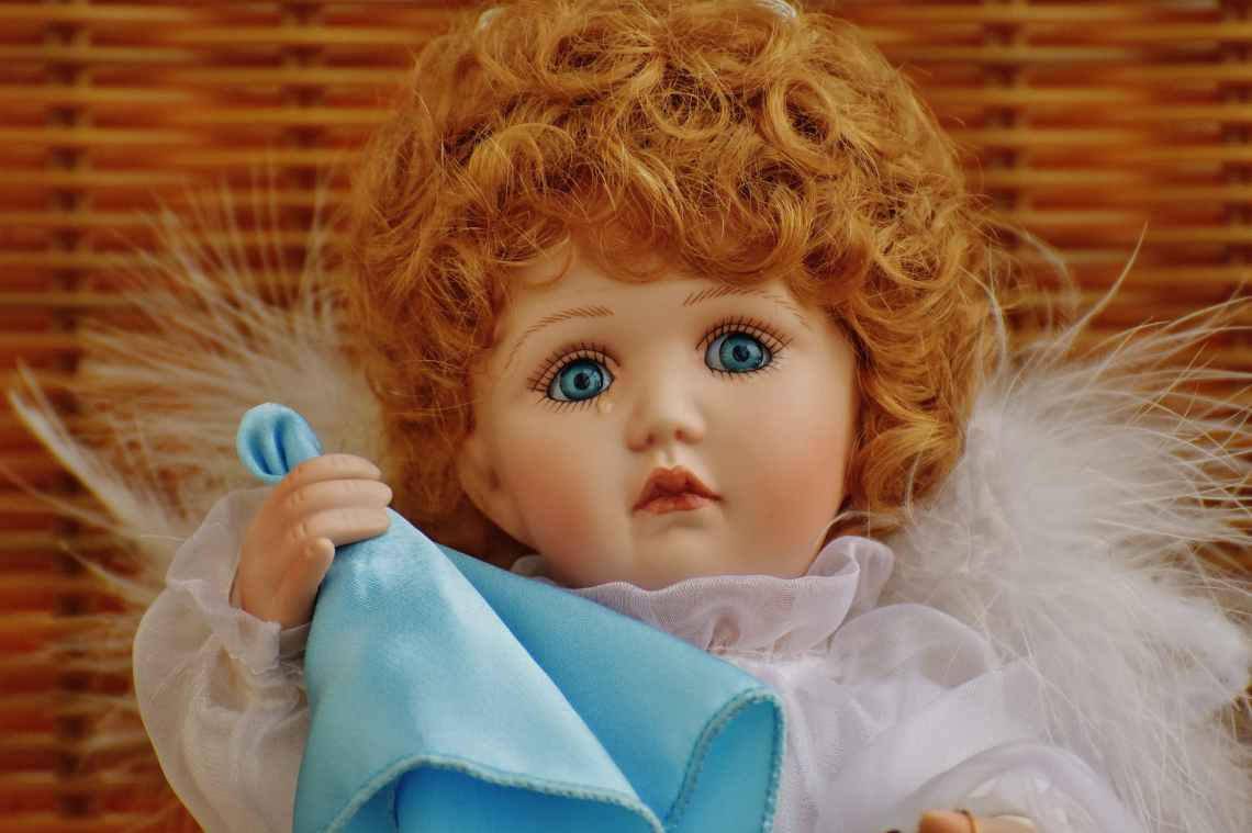 girl doll in white fur dress holding blue handkerchief