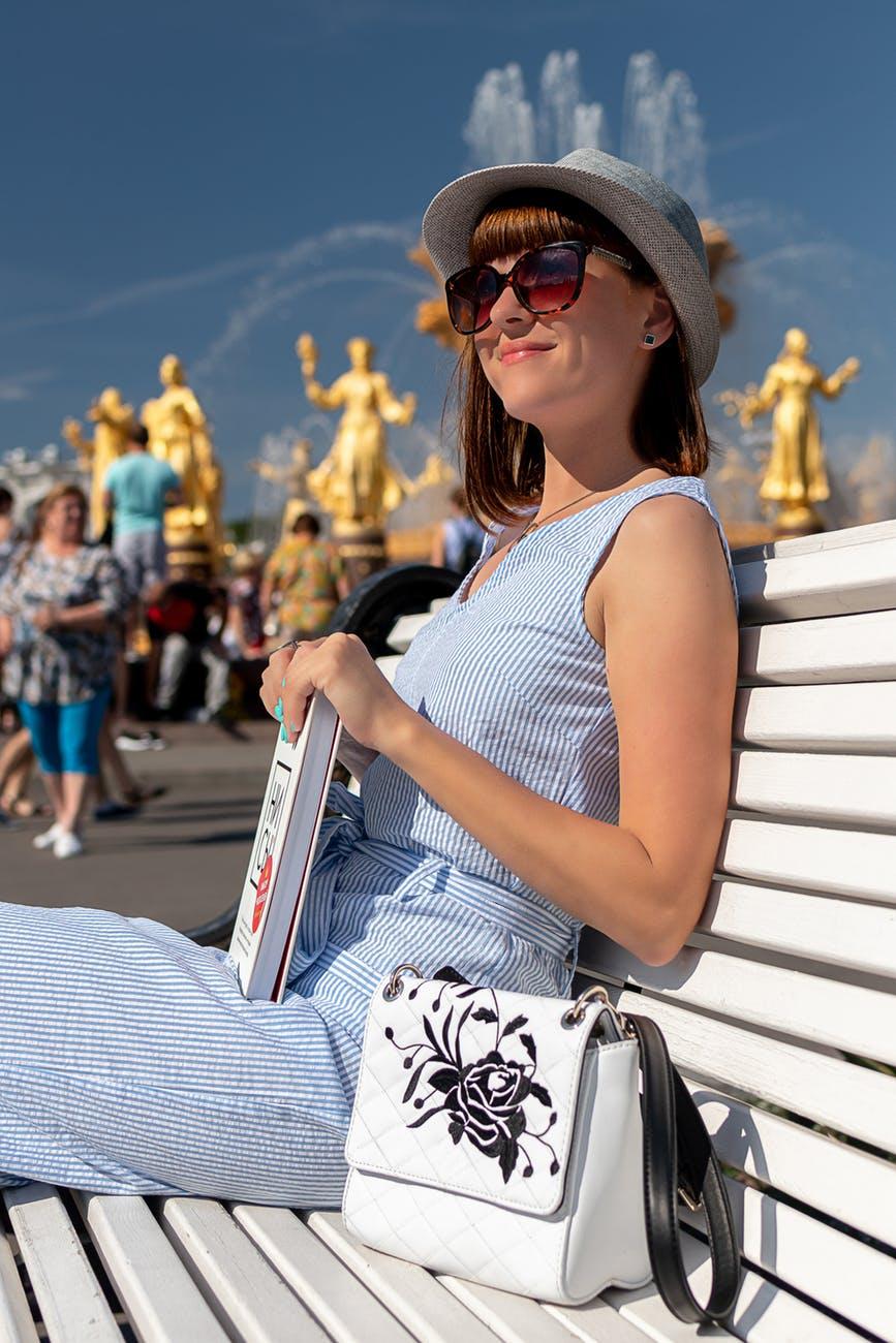 woman wearing white tank top sitting on bench